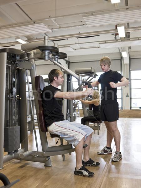 Man instructing how to use an exercise machine Stock photo © gemenacom