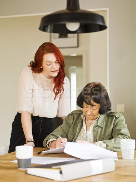 Segítő kéz fiatal nő segít nagymama papírmunka nők Stock fotó © gemenacom