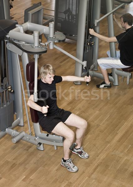 Young man using an exercise machine Stock photo © gemenacom