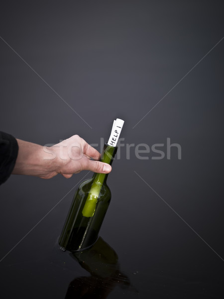 Hand picking up a bottle with a message in it. Stock photo © gemenacom