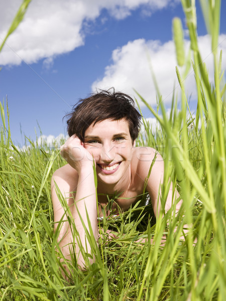 Smiling woman lying down in the grass Stock photo © gemenacom