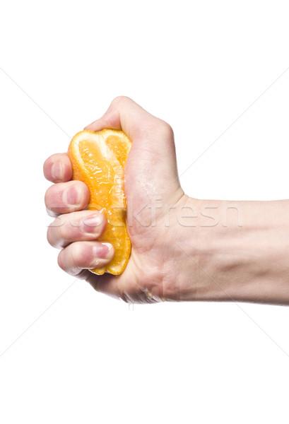 Hand squeezing an orange towards white background Stock photo © gemenacom