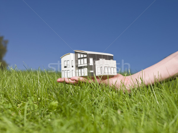 Man holding a miniature house outside in the sun. Stock photo © gemenacom