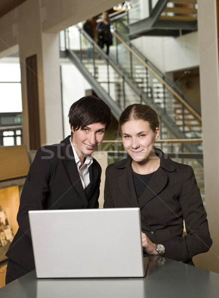 Two businesswoman in front of a computer facing the camera Stock photo © gemenacom