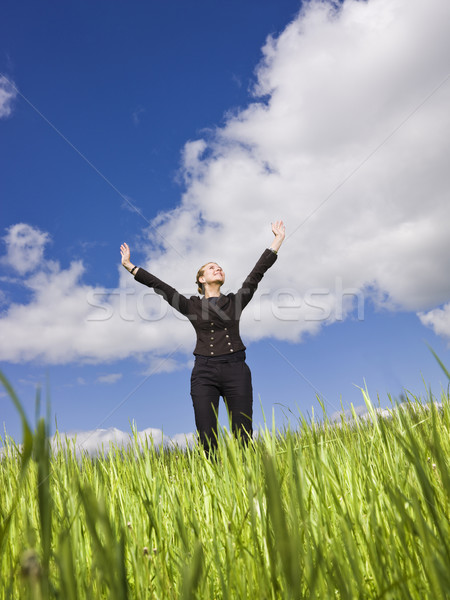 Young woman standing in the grass towards blue sky Stock photo © gemenacom