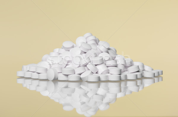 Stack of pills towards Yellow background Stock photo © gemenacom