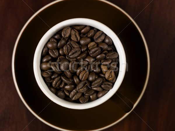 High angle view of coffee beans in a cup with a wooden backgroun Stock photo © gemenacom