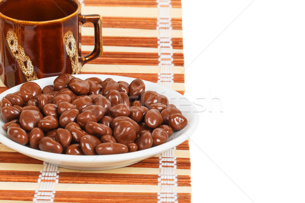 Chocolate dragees in a white saucer on a bamboo mat Stock photo © GeniusKp
