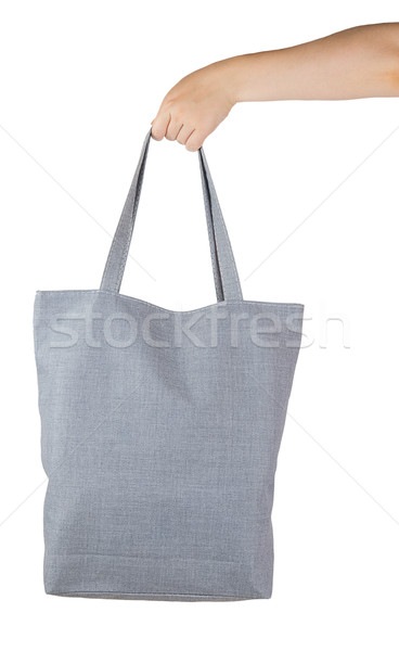 Female hand holding a gray textile shopping bag Stock photo © GeniusKp