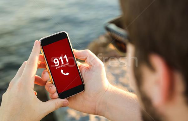 Homme téléphone portable côte urgence appel smartphone Photo stock © georgejmclittle