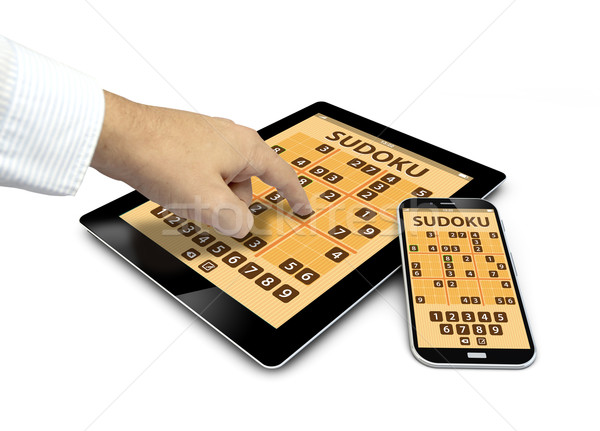 group of touchscreen devices with sudoku game and a finger touch Stock photo © georgejmclittle