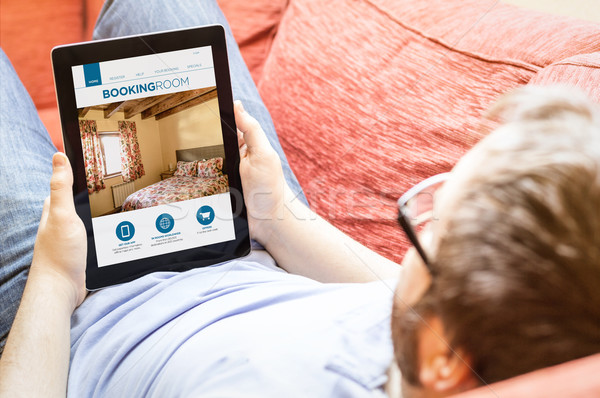 hipster on the sofa with booking web at tablet Stock photo © georgejmclittle