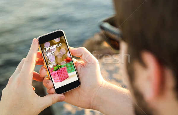 Man using his mobile phone on the coast to shop christmas gifts  Stock photo © georgejmclittle