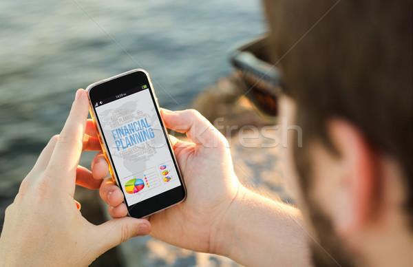 Homme téléphone portable côte planification financière smartphone tous Photo stock © georgejmclittle