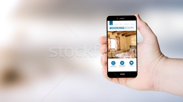 mobile phone booking web on user´s hand Stock photo © georgejmclittle