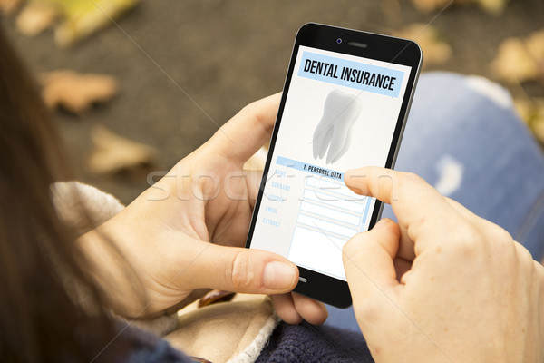 woman with dental insurance phone in the park Stock photo © georgejmclittle
