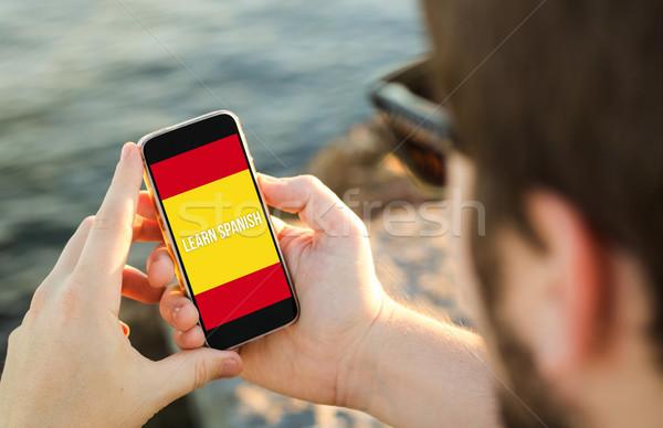Homme téléphone portable côte apprendre espagnol smartphone Photo stock © georgejmclittle