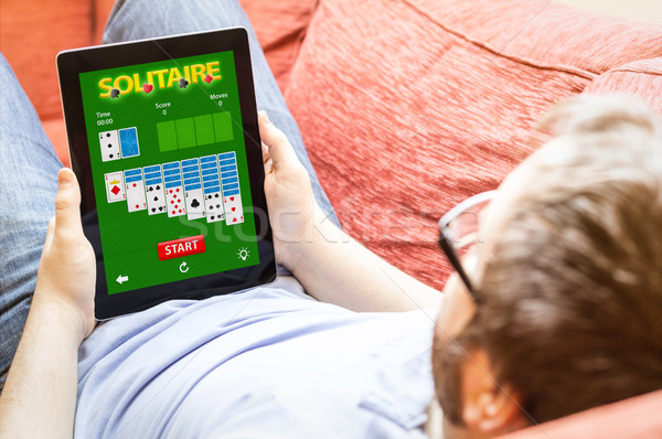hipster on the sofa with solitaire app tablet Stock photo © georgejmclittle