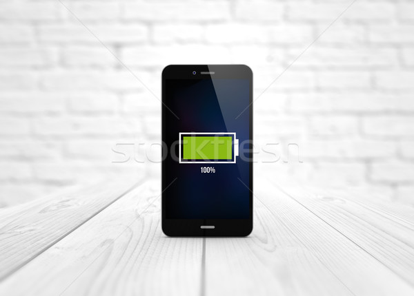 smart phone over wooden table full battery Stock photo © georgejmclittle