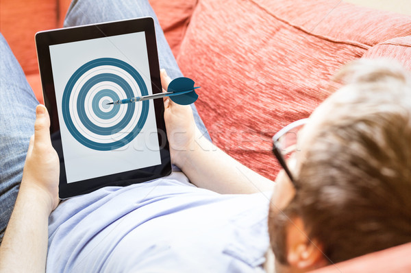 hipster on the sofa with dart board tablet Stock photo © georgejmclittle