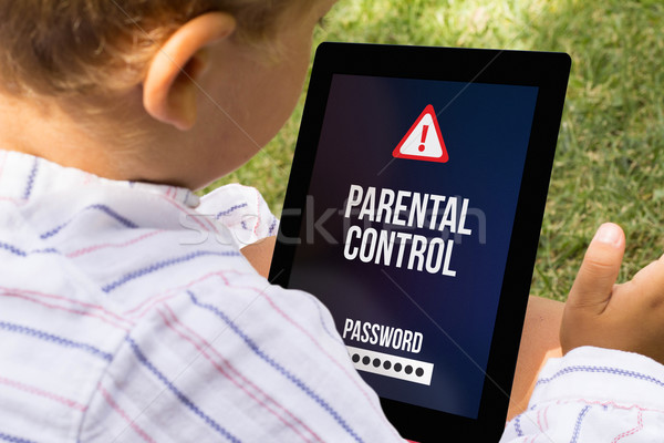 Stock photo: Boy with locked tablet
