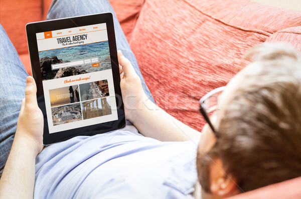 hipster with tablet with travel agency website on screen Stock photo © georgejmclittle