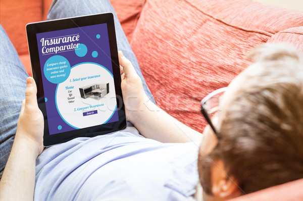 hipster on the sofa with insurance comparator tablet Stock photo © georgejmclittle