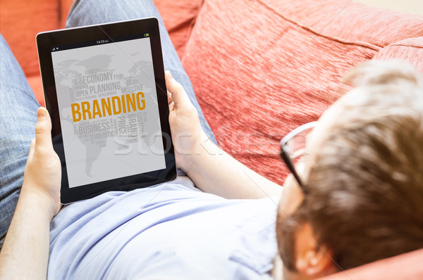 hipster on the sofa with branding tablet Stock photo © georgejmclittle