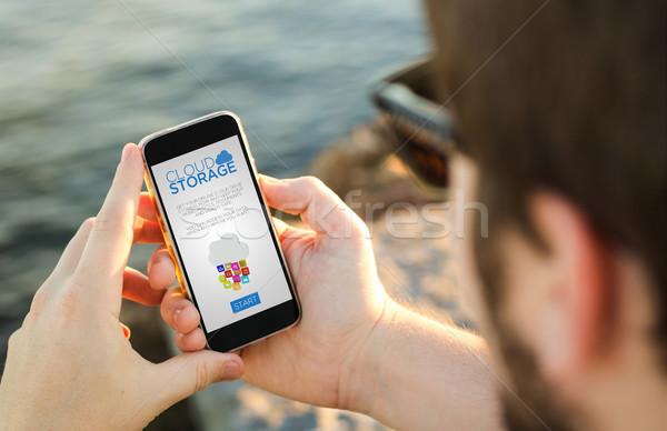 Man mobiele telefoon kust wolk opslag smartphone Stockfoto © georgejmclittle