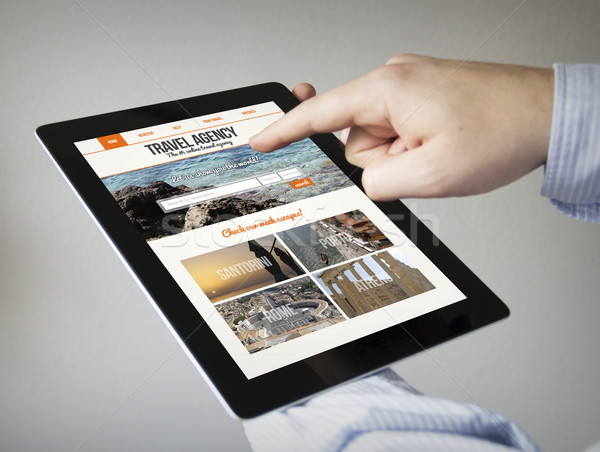 travel agency website on screen on a tablet Stock photo © georgejmclittle