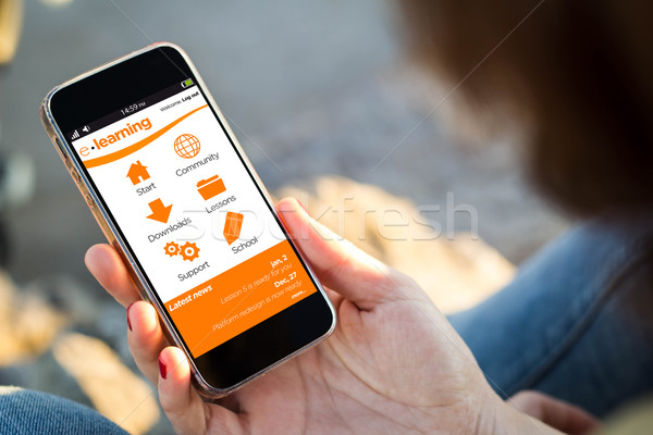woman sitting in the street holding her smartphone with e-learni Stock photo © georgejmclittle