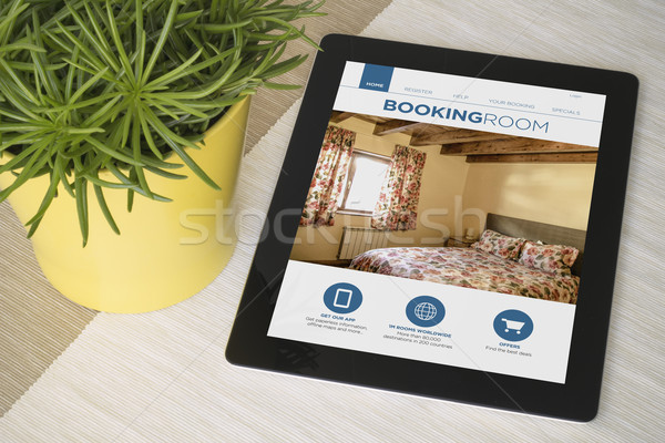 Tablet booking over a table with plant Stock photo © georgejmclittle