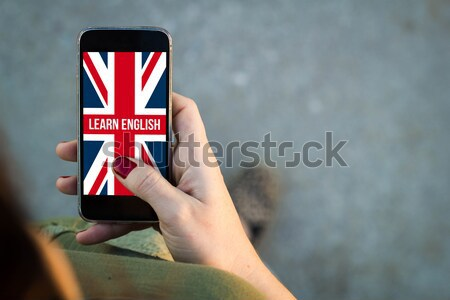 Man using his mobile phone on the coast to learn  english Stock photo © georgejmclittle