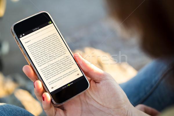 Kadın oturma sokak e-kitap Stok fotoğraf © georgejmclittle