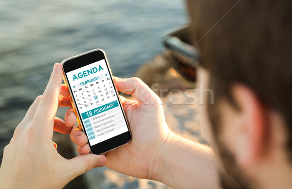 Man using his mobile phone on the coast to check memo organizer Stock photo © georgejmclittle