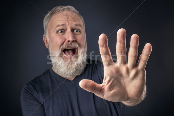 Panicked old man with his stretched hand forward Stock photo © georgemuresan