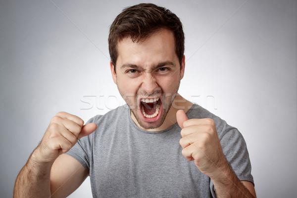 Joven enojado cara modelo boca Foto stock © georgemuresan