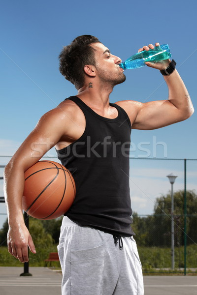 Jonge man drinken mineraalwater basketbalveld water Stockfoto © georgemuresan