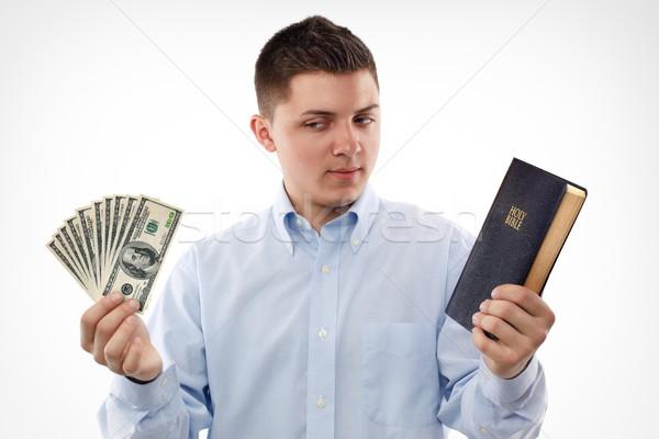 Szív fiatalember Biblia néz dollár bankjegyek Stock fotó © georgemuresan