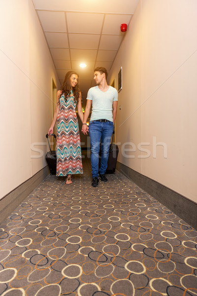 Young couple standing at hotel corridor upon arrival, looking for room, holding suitcases. Stock photo © Geribody
