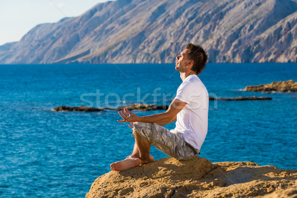 Handsome man in a yoga position on the beach Stock photo © Geribody