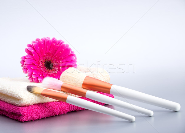 Brushes for make-up  on towel with  big pink flower Stock photo © Geribody