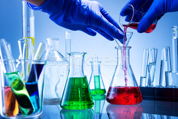 Laboratory equipment, lots of glass filled with colorful liquids, hand poured Stock photo © Geribody