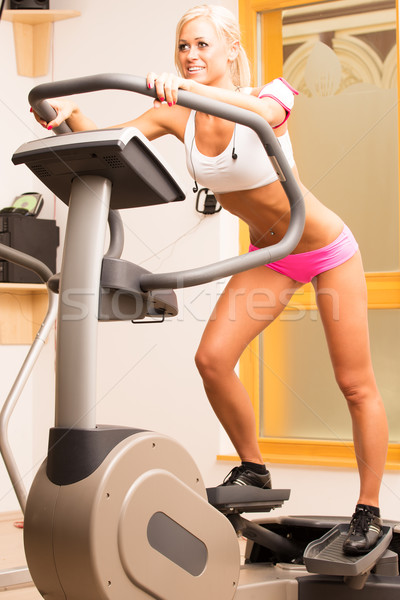 Stock photo: An attractive young woman using a step machine in the gym