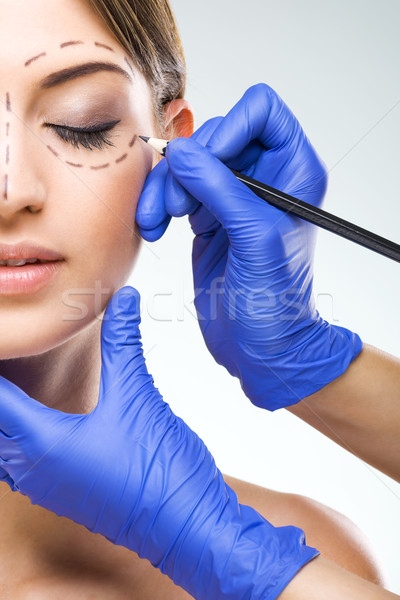 Beautiful woman half face photo plastic surgery, plastic surgeon hands  Stock photo © Geribody