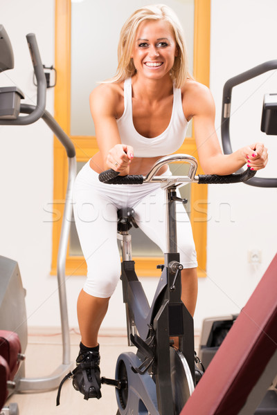 A stunning young woman using an exercise bike in the gym Stock photo © Geribody