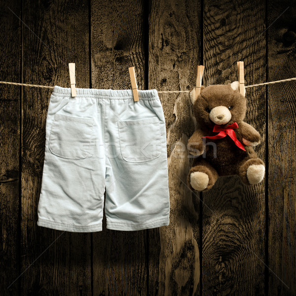 Baby clothes and a teddy bear on clothesline Stock photo © Geribody