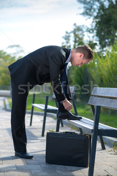 Young businessman with tie his shoelace Stock photo © Geribody
