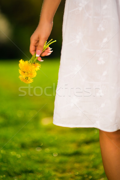 Smiling young woman holding some flowers happily Stock photo © Geribody
