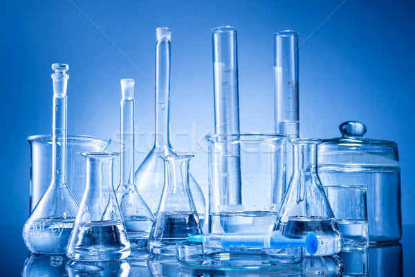 Laboratory equipment, bottles, flasks on blue background Stock photo © Geribody